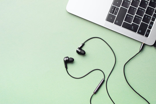 Headphones connected to a laptop with wires and a control panel lie on a mint green background.