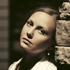 Sad beautiful fashion woman leaning on the wall in night city street