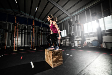 Athletic girl does box jump exercises at the gym