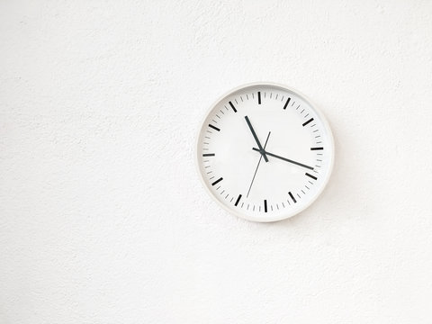 Simple modern round clock on white wall