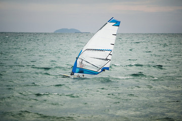 windsurfer floating on board at sea.