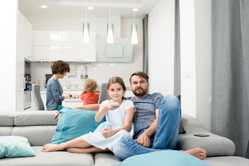 Portrait of bearded father watching TV with daughter sitting on sofa at home, mother and son in background, copy space