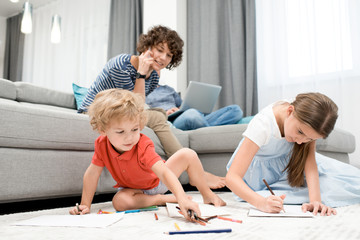 Portrait of two children drawing pictures sitting on carpet in living room with mom watching them from sofa