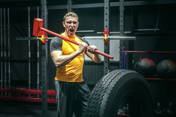 Hard training man strikes a big tyre by a hammer in his hands. Shock power training.