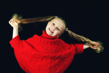 Adorable little blonde girl with long hair on dark background