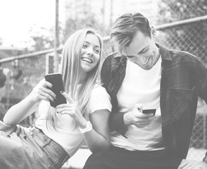 Happy cute young couple in the park using smartphones together