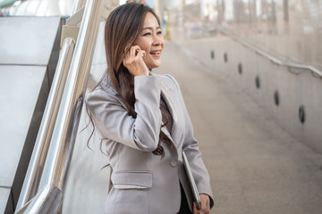 Senior business woman talking on mobile phone with client.
