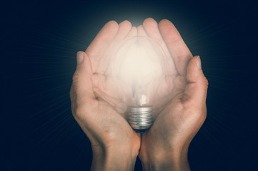 Glowing light bulb in female hands isolated on black