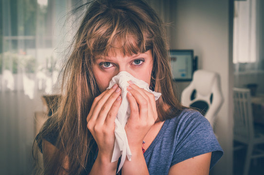 Sick woman with flu or cold sneezing into handkerchief