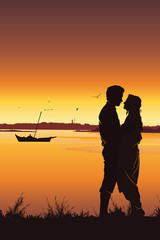 Silhouette of young romantic couple on sunset background.