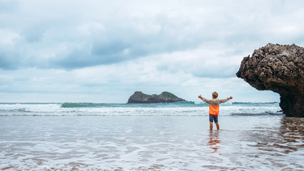 Boy enjoy with fresh wind on the ocean surf line after rain
