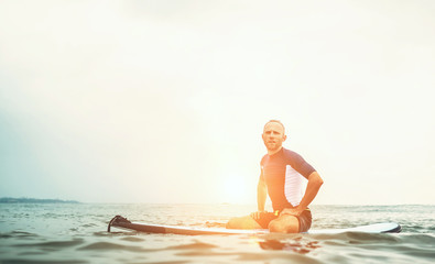 Man surfer sits on surf board in the water and  waits waves