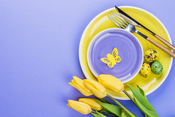 Holidays Spring Background. Easter table setting with spring tulips, colorful quail eggs and cutlery on purple background. Top view, flat lay, copy space