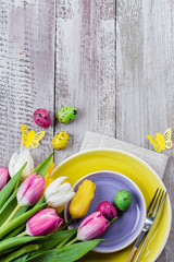 Holidays Spring Background. Easter table setting with spring tulips, colorful quail eggs and cutlery on shappy wooden background. Copy space, top view