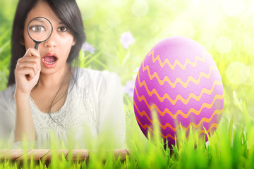 Young asian woman with magnifier finding easter egg