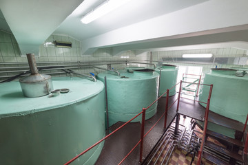 Large metallic cisterns of green color. Manufacture of alcoholic beverages.
