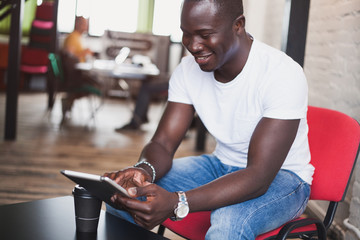 Smiling African man using tablet for video conversation in modern office.