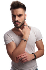 portrait of a cools guy holding hand on neck