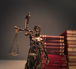 justice statue in front of a pile of law books
