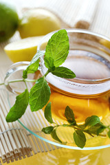Tea in the glass cup with lemon and fresh mint leaves - herbal healing tea as homemade remedy