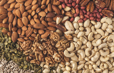 A variety of nuts and seeds background, food background, vegan healthy food concept. Copy space, top view.