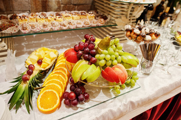 Close-up photo of a huge variety of fruits and sweet desserts on the wedding banquet.