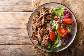 Delicious food: slow cooked pulled beef with fresh vegetable salad close-up. Horizontal top view from above Wall mural