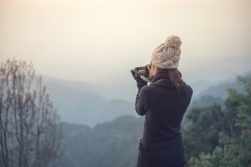 Traveler woman take photo view of mountain with mirrorless camera.