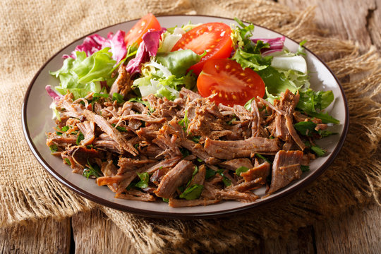 spicy pulled beef with vegetable salad close-up on a plate on a table. horizontal