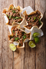 Pulled beef with lime and greens in a corn tortillas close-up on a table. Vertical top view