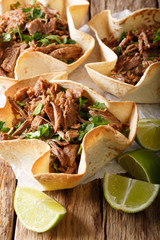 Mexican barbacoa with beef, lime and greens close-up on paper on table. vertical