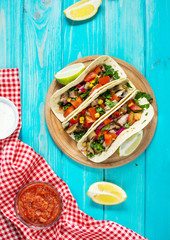 Mexican pork tacos with vegetables. Tacos al pastor on wooden blue rustic background. Top