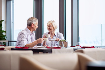 Sweet conversation. Sincere attractive mature couple drinking coffee while chatting and sitting at the restaurant