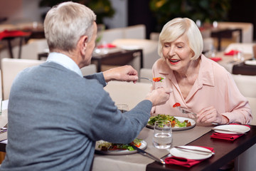 So sweet. Happy jolly mature woman opening mouth while leaning on table and looking at fork