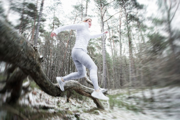 Motion blurred woman exercise outdoors in winter