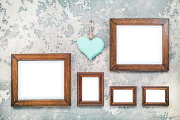 Photo or picture frame blanks and wooden handmade Valentine's day love heart hanging on vintage aged grunge textured concrete wall background. Retro old style filtered photo
