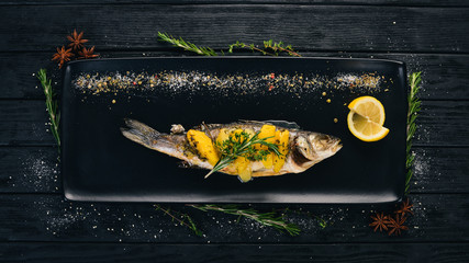 Fish sibas baked with vegetables and citrus fruits. On a black wooden background. Copy space.