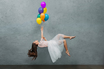 young woman levitating with colorful balloons
