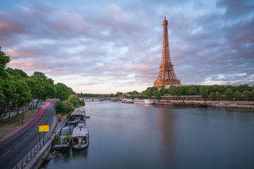 Long exposure photographyof the Eiffel Tower from Seine river in the evening time with parking boat at her bank