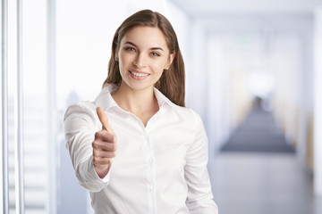 Beautiful young businesswoman with toothy smile giving thumbs up while standing at the office.