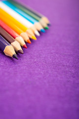 Nine multicolored pencils on a purple felt background. Different colored pencils with space for text. Back to school. Art lessons.