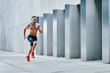 Handsome shirtless athlete jogging outside in modern urban setting