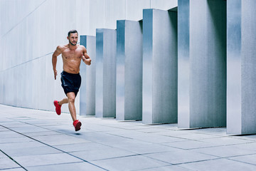 Handsome young muscular man jogging in the city