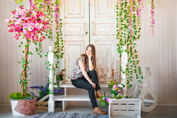 Beautiful spring photography in the decorated interior. A young woman in flowers on the doorstep of a house.