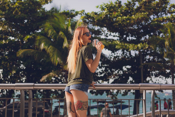 tattoed young woman in shorts drinking cocktail from plastic cup outdoors