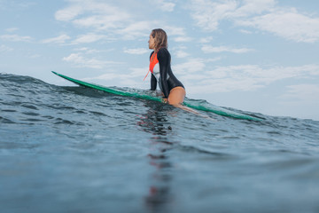 female surfer sitting on surf board in ocean
