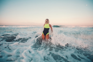 back view of sportswoman surfing on surf board in ocean