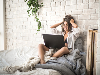 Excited beautiful woman with arms raised looking at her laptop screen