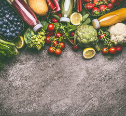 Healthy dieting and antioxidant beverages background with various colorful organic vegetables, fruits and berries smoothies with ingredients in bottles on gray granite table , top view with copy space