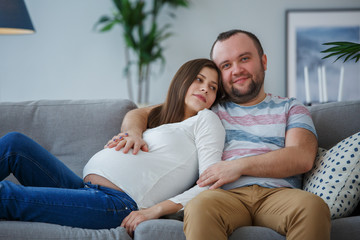 Photo of happy pregnant woman and man on gray sofa